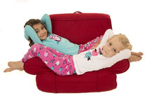 Two cute girls relaxing in a red chair Royalty Free Stock Photo