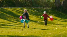 Two cute girls running on green meadow holding colorful balloons. Slow motion stock video footage