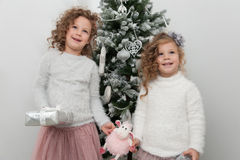 Two cute girls with sheep toy near Christmas tree Stock Image