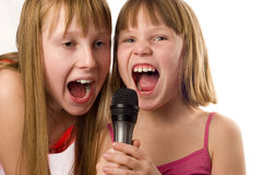 Two cute girls singing to microphone Stock Image
