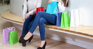 Two cute girls are sitting on a bench in the mall with gift bags . Royalty Free Stock Photos