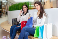 Two cute girls are sitting on a bench in the mall with gift bags. Stock Photos