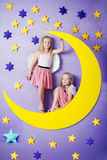 Two cute girls sitting on a big moon Royalty Free Stock Image