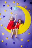 Two cute girls sitting on a big moon Royalty Free Stock Photo