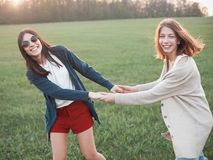 Two girls dancing at sunset. Two cute girls smiling and dancing at sunset. Best friends Royalty Free Stock Image