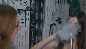Two cute girls smoke hookah stock video footage