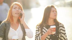 Two cute girls are at the street in the city. Girls are holding paper cups with coffee. Redheaded girl speaks on a. Mobile telephone. Her friend looks at his stock video footage