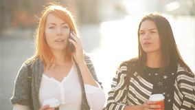 Two cute girls are at the street in the city. Girls are holding paper cups with coffee. Redheaded girl speaks on a. Mobile telephone. Her friend looks at his stock footage