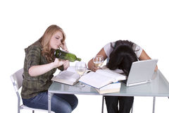Two cute girls studying at thier desks Royalty Free Stock Images