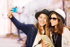 Two cute girls taking selfies with mobile phone Royalty Free Stock Image