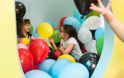 Two cute girls talking while playing with multicolored balloons. At kindergarten or at a modern playground Stock Photos