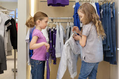 Two cute girls try on clothes in a modern store Stock Photos