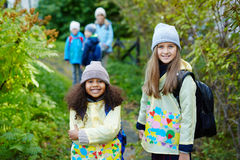 Two Cute Girls on the way to School in Autumn. Portrait of two schoolgirls with backpacks, one of them African-American, posing, smiling at camera on the way to royalty free stock photo