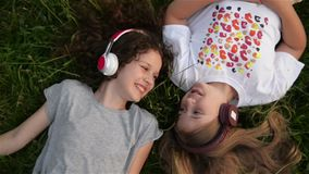 Two Cute Girls Wearing Headphones Lying In Park. Beautiful Kids School Age Are Having Fun Spending Time Together.
