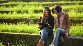 Two Cute Girls Wearing Jeans are Using Tablet Outdoors Sitting in the Park. Young Amazing Women are Looking at the. Screen of Electronic Gadget, HD stock video
