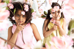 Two cute grils hiding herself behind branches. Two little grils hiding herself behind branches Stock Photo
