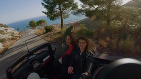 Traveling in convertible car for life. Two cute and happy excited young women, best friends make selfie photo or video of summer vacation trip, travel bloggers stock video