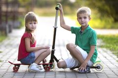 Two cute happy funny smiling young children, brother and sister, posing for camera, handsome boy with scooter and pretty long-. Haired girl sitting on skateboard royalty free stock photos