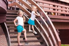 Two cute happy gilrs outdoor. On stairs Royalty Free Stock Images