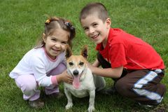 Two cute happy kids with dog. Two cute smiling happy kids with dog on a green lawn Royalty Free Stock Image