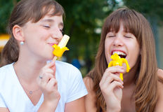 Two cute happy teenage girls eating ice cream Royalty Free Stock Photography