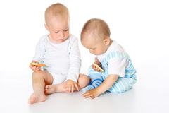 Two cute joyful children sitting together on white background isolated Stock Photos