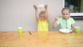 Two cute kid eating. At table stock footage