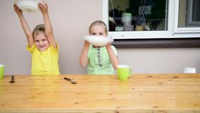 Two cute kid eating. At table stock video footage