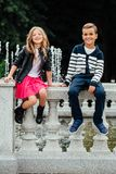 Two Cute Kids Are Sitting On The Railing. Marble-stone Fountain. Stock Photography