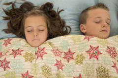 Two cute kids asleep under a snowflake blanket Stock Images