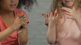 Two cute kids covering small hands in colorful paint, product safe for children stock footage
