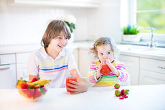 Two cute kids having fruit for breakfast drinking juice Stock Photography
