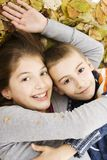 Two cute kids lying down with leaves around Stock Photo