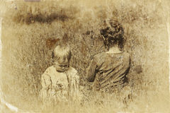 Two cute kids playing in field. abstract and dreamy concept. image is textured and old syle toned Stock Photos