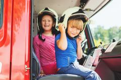 Two cute kids playing in fire truck
