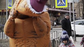 Two cute kids playing with person in T Rex costume at sidewalk. Two cute caucasian kids playing with person in T Rex costume at sidewalk. Cold sunny spring or stock video footage