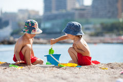 Two cute kids, playing in the sand on the beach. With toys Royalty Free Stock Images