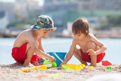 Two cute kids, playing in the sand on the beach. With toys Royalty Free Stock Photography