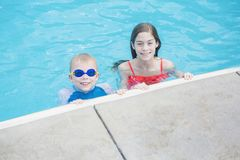 Two cute kids playing in a swimming pool on a sunny day Royalty Free Stock Image