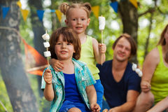 Two cute kids with roasted marshmallow at campsite Royalty Free Stock Photos