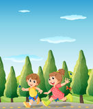 Two cute kids running at the road Royalty Free Stock Photo