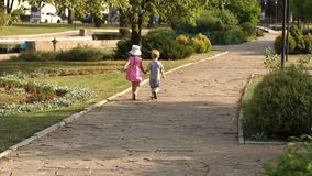 Two cute kids walking in the alley in summer Park. Two young children, a boy and a girl walking along the alley in the park in summer at sunset and holding stock footage