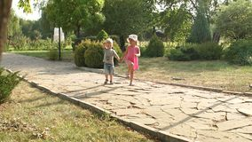 Two cute kids walking in the alley in summer Park. Two young children walk in the Park along the stone alley on a hot summer day at sunset. Slow motion stock video footage