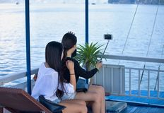 Two cute ladies make a selfie. Two young girls doing selfie on a sightseeing boat - Ha long bay Vietnamm Royalty Free Stock Photo