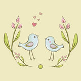 Two cute little birds are framed by flowers background Stock Image