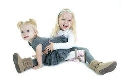 Two cute little blond sisters kneeling on the. Floor arm in arm cuddling each other in a loving embrace, on white Royalty Free Stock Photography
