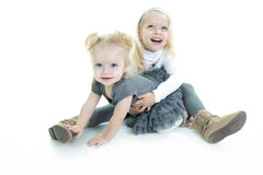 Two cute little blond sisters kneeling on the. Floor arm in arm cuddling each other in a loving embrace, on white Royalty Free Stock Photo