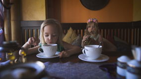 Two cute little blonde girls are having tea in a cafe. Happy childhood. Two pretty little blonde girls are having tea in a cafe. A sweet little girl with the stock video footage