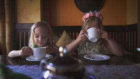 Two cute little blonde girls are having tea in a cozy cafe stock footage
