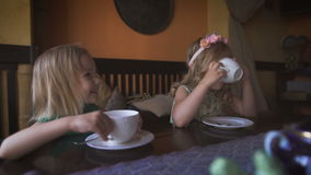 Two cute little blonde girls are having tea in a cozy modern cafe. Happy times. Two pretty little blonde girls are having tea in a cozy modern cafe. Little stock footage